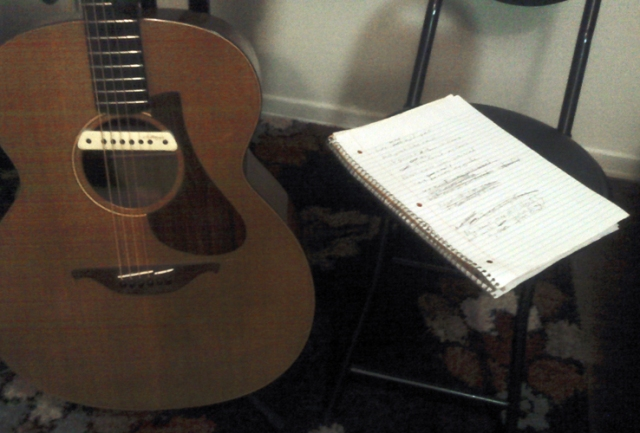 My guitar is in my bedroom and I have started writing a new song. The first verse is done and the lyrics are scrawled on that notebook next to my guitar.