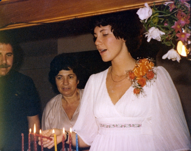 This picture is very special. I am lighting Hanukah candles and singing the blessing. My mom is behind me and Howard is on the left side. I still follow some rituals and Hanukah candle lighting is one of them.