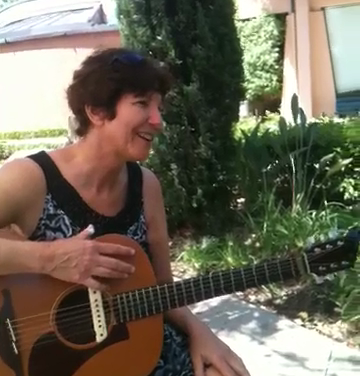 In this picture, I'm playing my guitar for my mother in the garden of her nursing home.