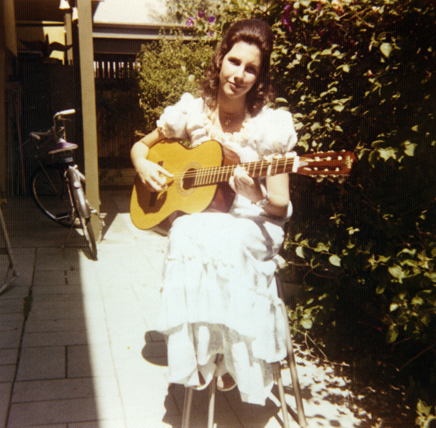 In this picture, I am playing guitar on the patio where I now live.